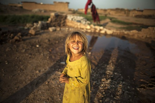 Zohra Bensemra A girl, whose family fled military operations in the western tribal area, smiles in a slum on the outskirts of Islamabad on July 8, 2013.jpg