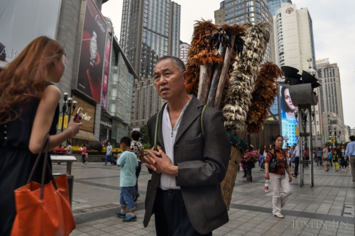justin-jin-Liu Yong, a 59-year-old former farmer, earns around 1,000 yuan a month selling chicken-feather dusters in the centre of Chongqing city in southwestern China. His village was razed several years ago.jpg