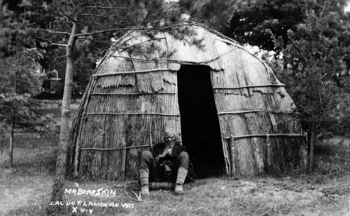 Lac du Flambeau medicine man Mr. Bearskin in front of an Ojibwe wigwam, early1900's.jpg