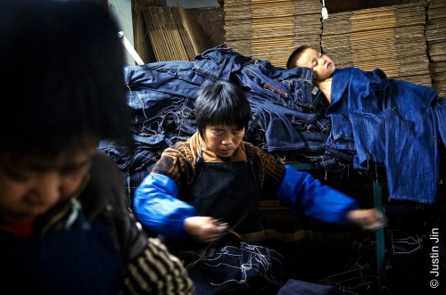 Justin-JinA child sleeps on a pile of jeans. The son of migrant workers, he has no place at local schools..jpg
