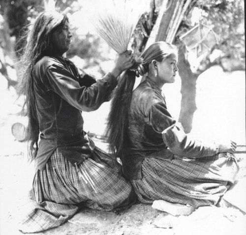 Navajo (Diné) mother tying her daughter's hair using brush. Undated .jpg