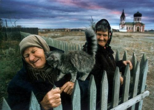Igor Lagunov A kitten loves on an old woman in the Cossack village of Velikopetrovskaya near Cheliyabinsk. .jpg