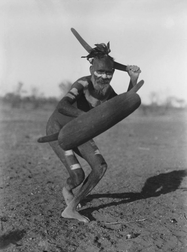 Luritja man demonstrating method of attack with boomerang under cover of a shield, Australia, 1920.n.jpg