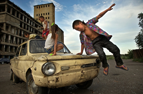 Justin Jin-Children play on a beaten Lada outside derelict factory in Tuva.jpg