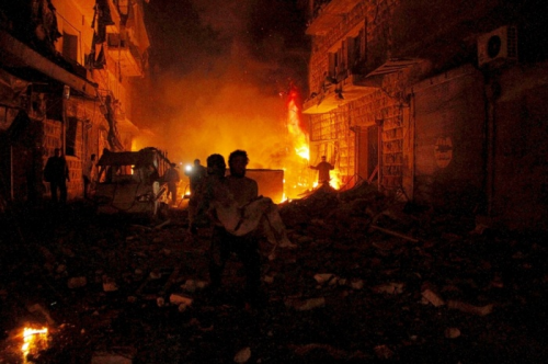 sultan Kitaz a man carries an injured person after what activists said was shelling from forces loyal to Syria's president Bashar al-Assad in Aleppo.png