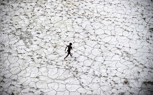Sanjay Kanojia An Indian street child plays in a dry river bed after flood waters receded in Allahabad on October 25, 2013.jpg