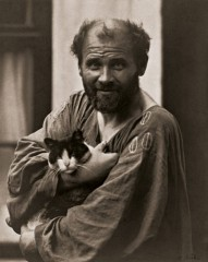 gustav klimt wearing his painter's coat in front of his studio holding one of his cats circa 1912.jpg