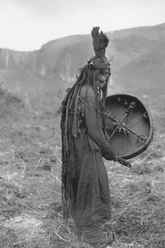 Mongolian shaman wearing a ritual gown and holding a drum with the image of a spirit helper,c. 1909.jpg