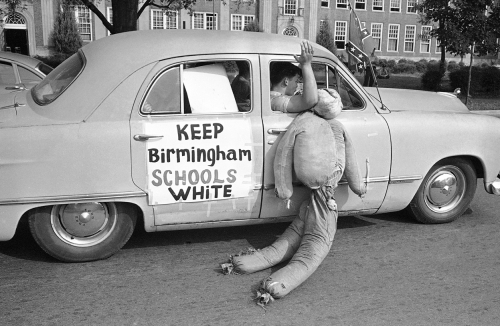White students in Birmingham, Alabama, drag an African American effigy past West End High School, on September 12, 1963.jpg