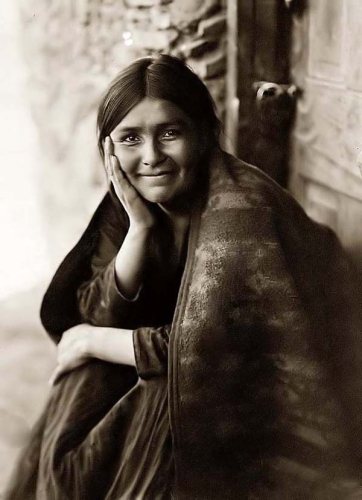 Edward S Curtis Navaho woman sitting outside her doorway 1904.jpg