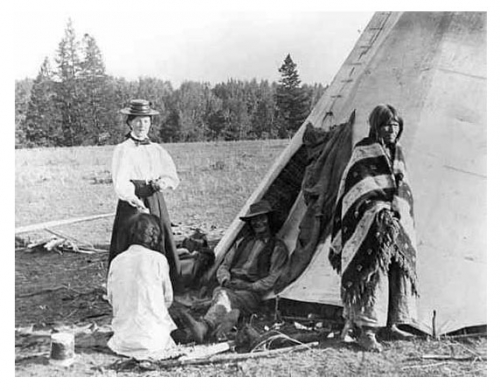 Frances Densmore with American Indians outside of a tipi, 1900.jpg