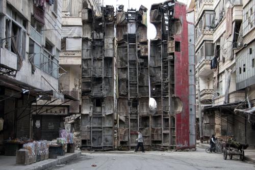 Karam Al-Masri Un garçon passe devant une barricade faite de carcasses de bus à Alep_n.jpg