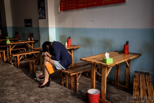 justin-jin-A woman from the countryside falls asleep at work in a restaurant in the heart of a relocation housing estate in China's southwestern Chongqing city.jpg