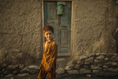Zohra Bensemra-A boy walks past a muddy house in a slum on the outskirts of Islamabad, Pakistan on September 5, 2013..jpg