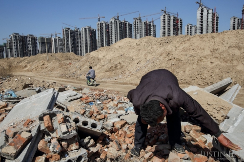 justin-jin-Li Rui, 60, scavenges for building materials at the site of his former village in the northeastern province of Shangdong, chine now bulldozed into a giant construction site.jpg