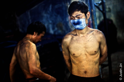 Justin-Jin-jeans-Workers take a break after scrubbing jeans all night in Mr Huang's factory. The blue dust that fills the air clogs lungs despite masks..jpg