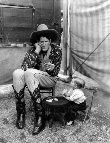 Jack Earl, the Cowboy Giant and Midget Mite playing cards behind the tent line of Ringling Bros. show. (1934)_n.jpg